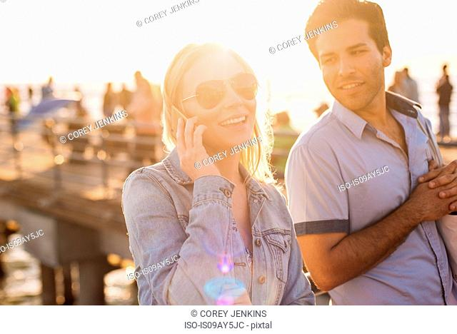 Young couple on sunlit pier chatting on smartphone, Santa Monica, California, USA