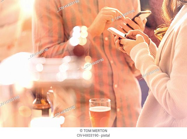 Man and woman texting with cell phone and drinking beer at bar