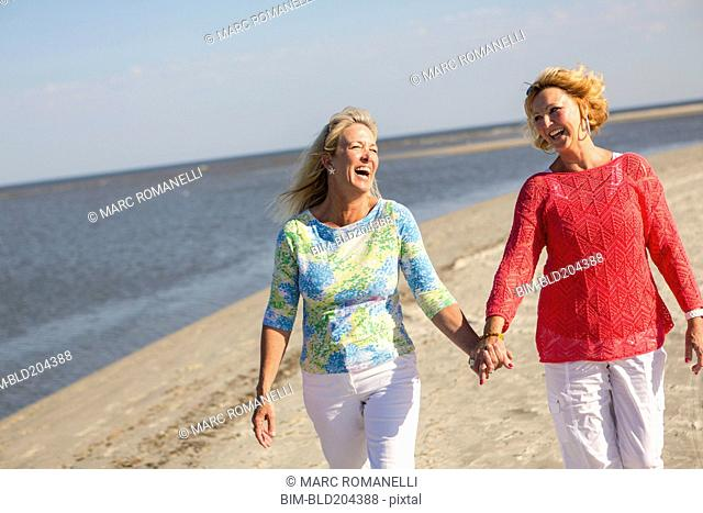 Caucasian women walking on beach
