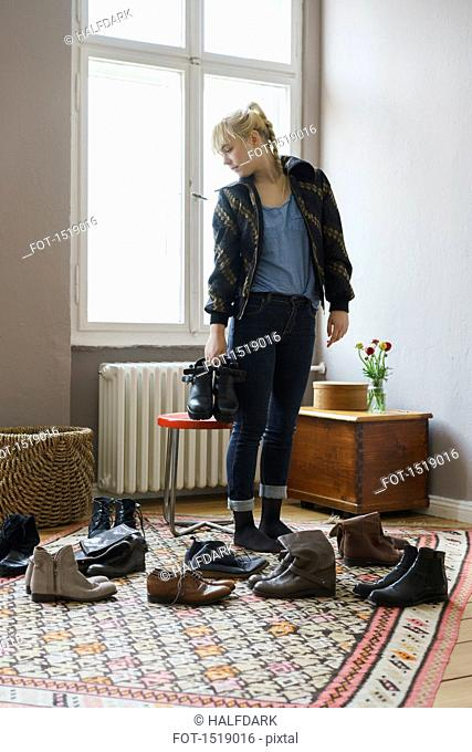 Young woman choosing shoes while standing in living room at home