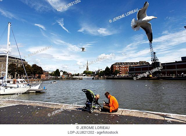 A father and child sit beside the River Avon at Harbourside in Bristol