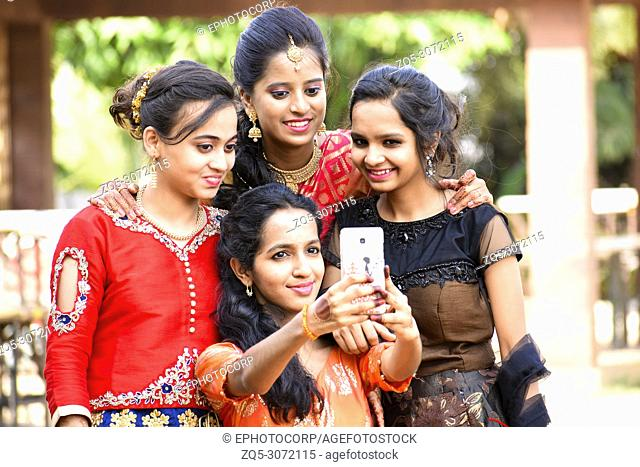 Group of well dressed girls taking selfies on phone, Pune, Maharashtra