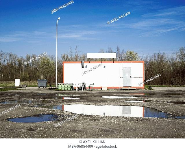 White accomodation container in a forest with puddles in the foreground