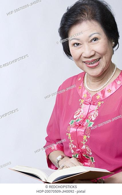 Portrait of a senior woman holding a book and smiling