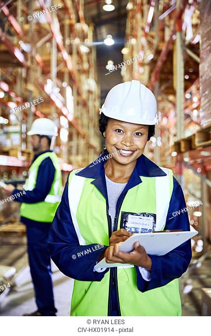 Portrait confident female manager with clipboard in distribution warehouse