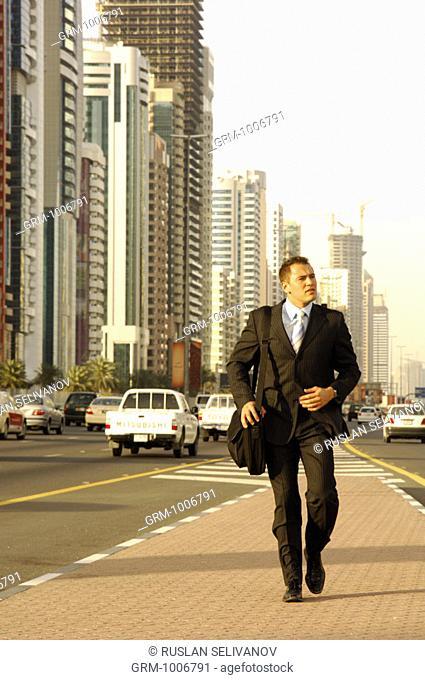 Businessman walking on Shaikh Zayed Road in Dubai