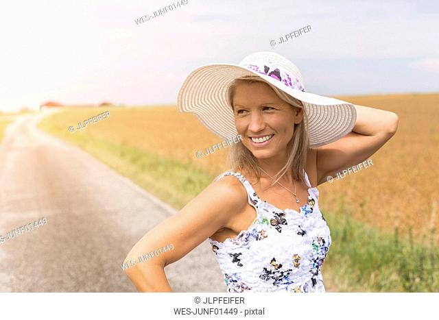 Smiling mature woman on remote country lane in summer