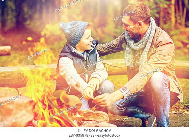 camping, tourism, hike and family concept - happy father and son roasting marshmallow over campfire