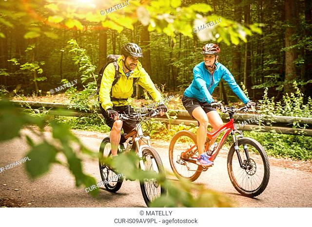 Mature mountain biking couple cycling along rural forest road