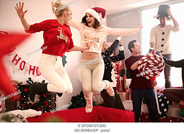 Young women jumping on sofa at christmas party