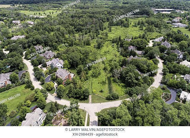 Aerial view of a luxury neighborhood with mature trees and a nature area in a Chicago suburban neighborhood in summer. Lake Forest, IL. USA