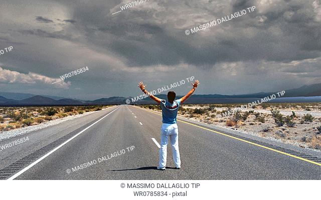 Man stading on empty highway