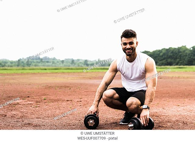 Portrait of smiling athlete with dumbbells on sports field