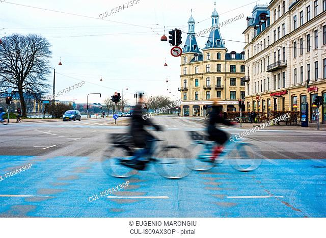 Two cyclists speeding along blue city cycle path, Copenhagen, Denmark