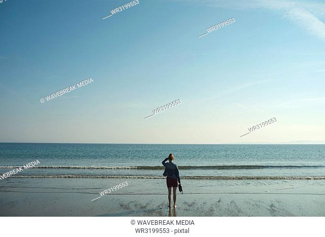 Woman standing on the sea beach on a sunny day