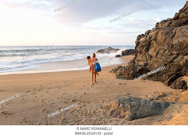 Caucasian mother carrying son on beach