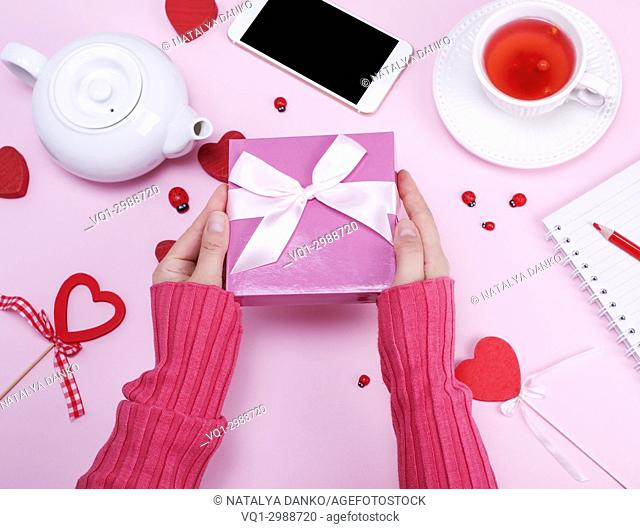 female hands hold packed box with a pink bow on the pink surface with a cup of tea and teapot, top view