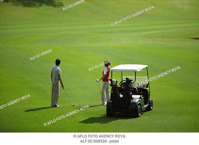 Couple Standing by a Golf Cart on a Fairway