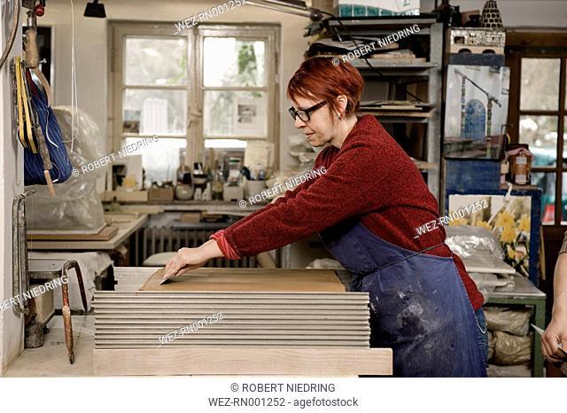 Germany, Bavaria, Mature woman preparing slices of clay in workshop