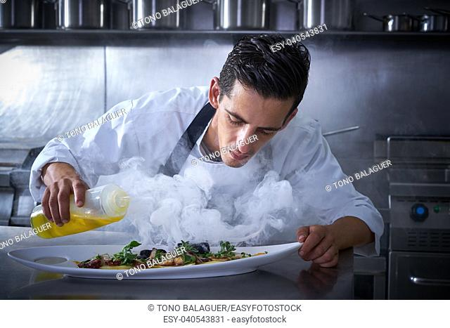 Chef working in kitchen with smoke and oil at restaurant