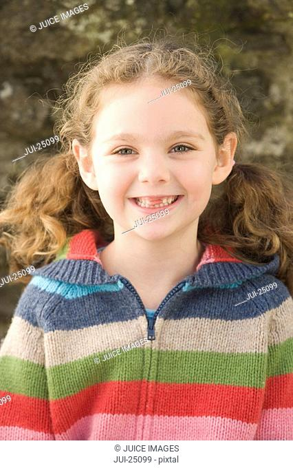 Smiling girl in sweater with front teeth missing