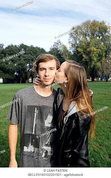Portrait of boyfriend and girlfriend (16-17) showing affection in park