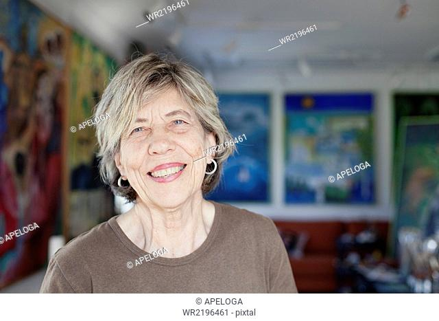 Portrait of smiling senior female artist in art studio