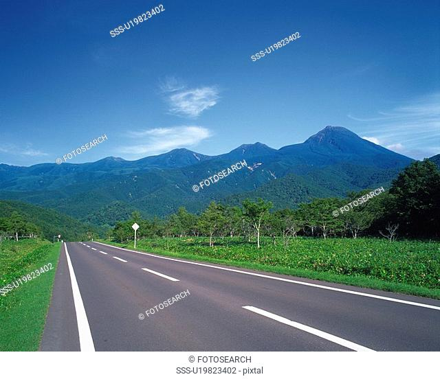 a Road, Surrounded By Mountains and Several Trees, Hokkaido Prefecture, Japan