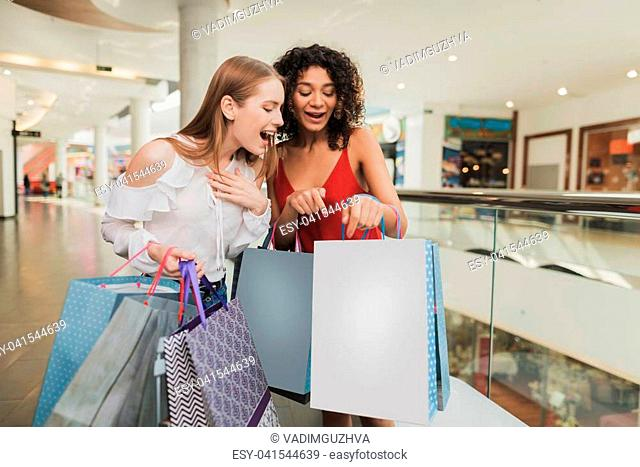 Girls are shopping at the mall. Sale in black Friday. Girls are shopping on a black Friday. The girls show each other the clothes they bought