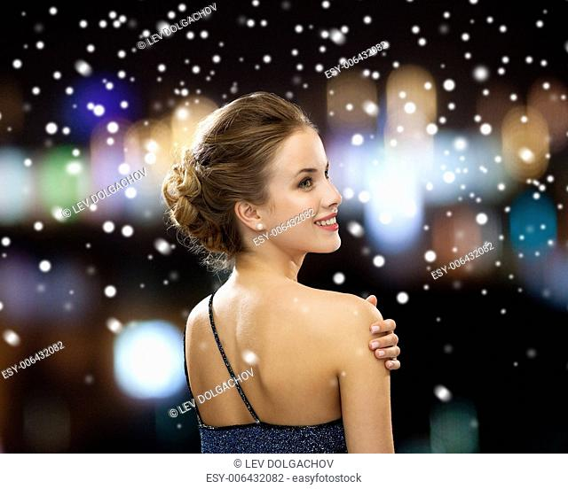 people, holidays, christmas and glamour concept - smiling woman in evening dress over black background over night lights and snow background