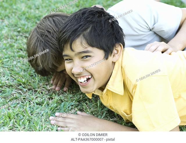 Preteen boys on ground, laughing