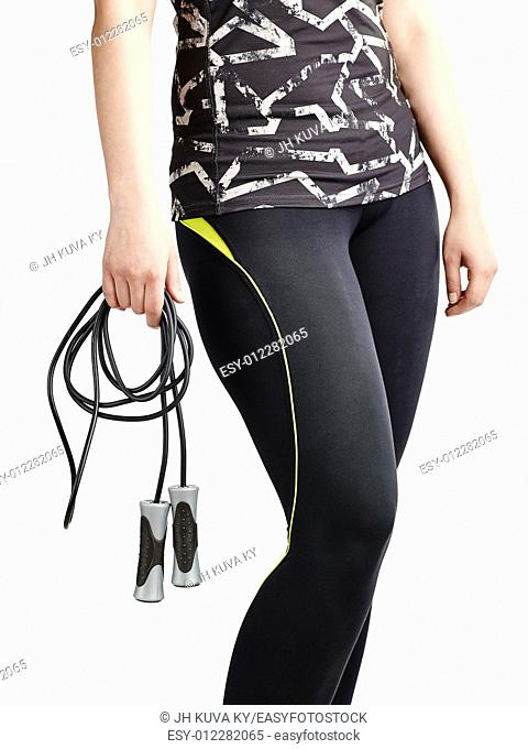 Sporty girl wearing a sportswear and she holding a skipping rope, white background