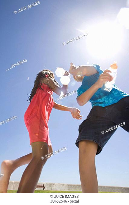 Children squirting water at each other at park