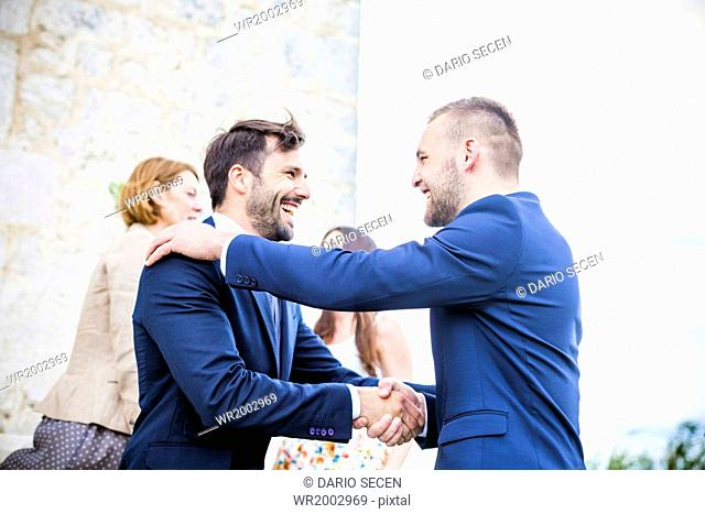 Bridegroom shaking hands with friend