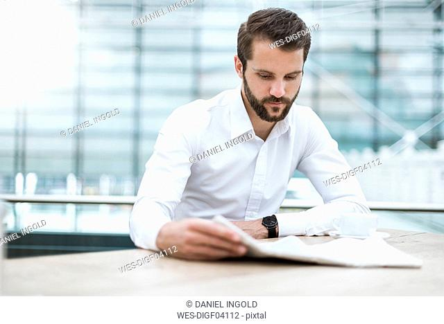 Young businessman reading newspaper in a cafe