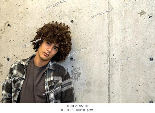 Portrait of teenage boy by concrete wall