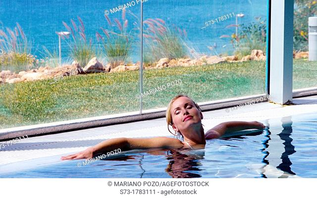 Woman bathing in swimming pool of spa center