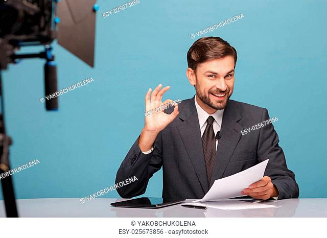 Cheerful male reporter is telling good news at the camera in studio. He is showing okay sign and smiling. The man is sitting at the table and holding documents