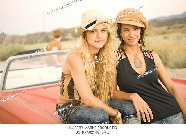 Two young women sitting on hood of car