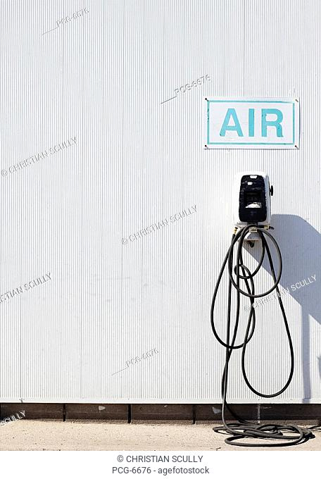 A garage, or truckstop. A sign. Air, for inflating car tyres. Tires. An air pressure pump. Tubing and nozzle. Gauge