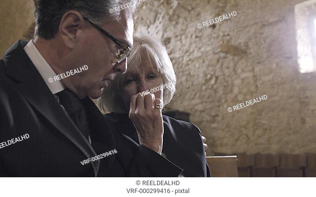 Grandmother crying at a funeral with granddaughter