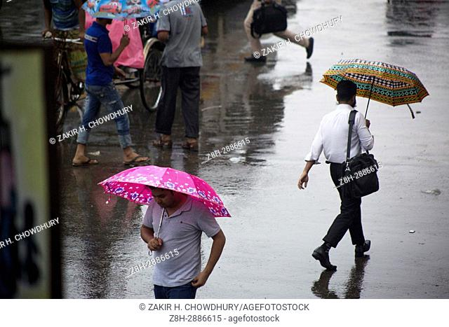 DHAKA, BANGLADESH - JUNE 05 : After offce Bangladeshi people back home using umbrella during rain in Dhaka, Bangladesh on June 05, 2017