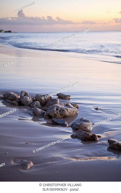 Caribbean sea washing over beach and rocks, Grand Cayman, Cayman Islands