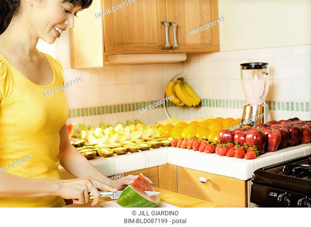 Mixed race woman cutting watermelon in kitchen