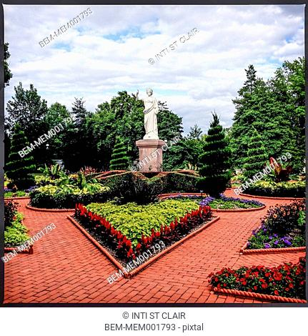 Statue over manicured gardens in park
