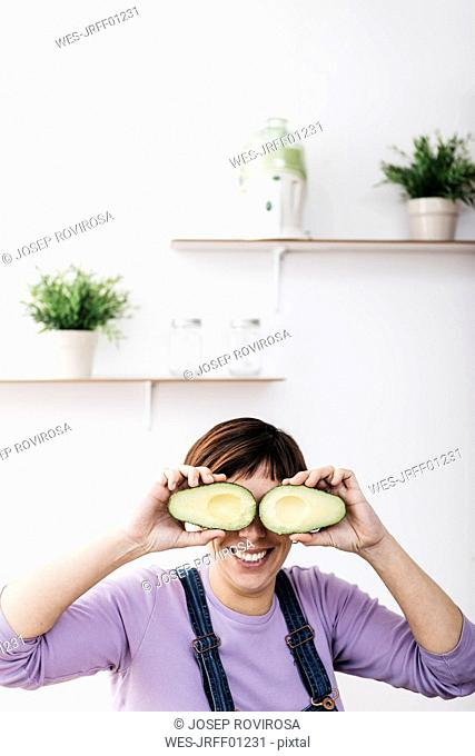 Smiling woman covering her eyes with halves of avocado