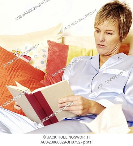 Close-up of a mature woman lying on the bed and reading a book