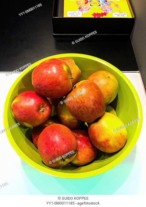 Breda, Netherlands. Green bowl with red apple's on the counter of a design museum