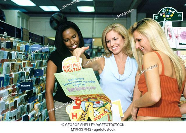 Friends buying greeting card at shop