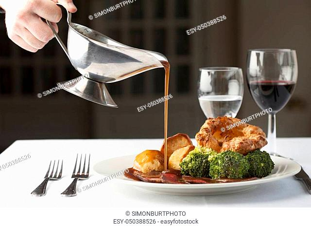 Traditional British roast dinner of rare beef, yorkshire pudding, roast potatoes and brocolli with gravy being poured over from a gravy boat